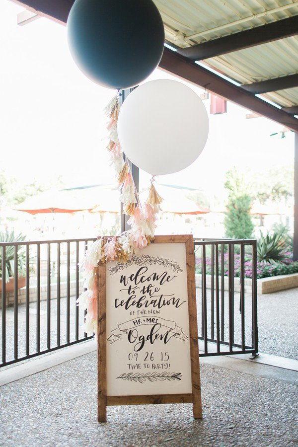 wedding entrance sign decorated with balloons