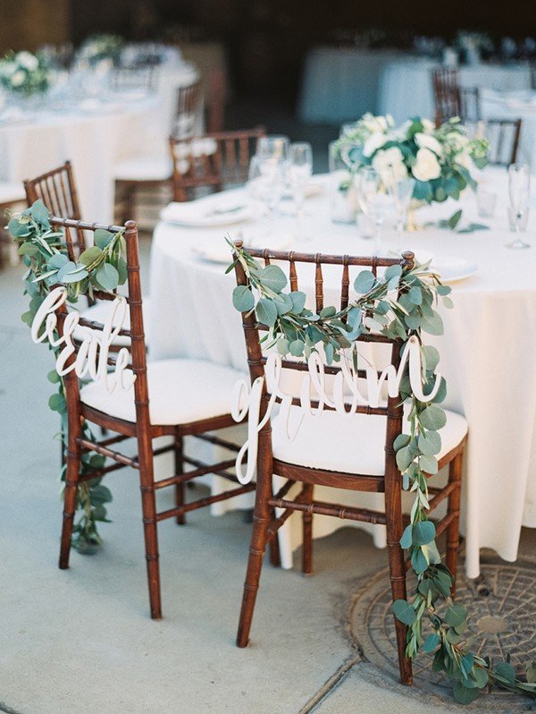 chic greenery decorated bride and groom chairs