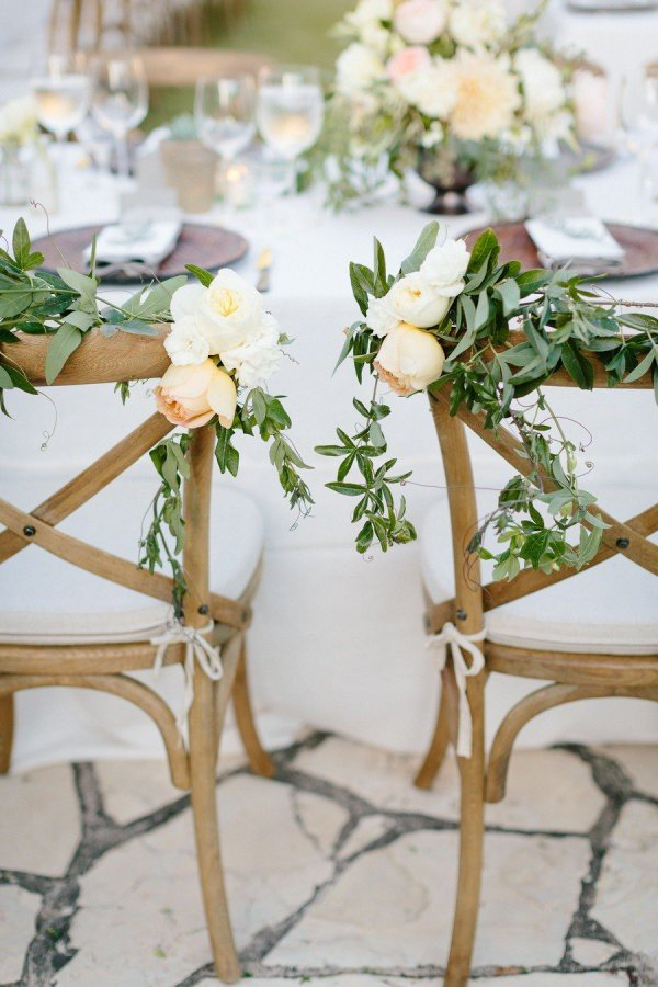 greenery and flower decorated bride and groom wedding chairs