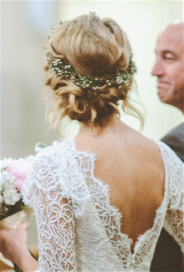 A Twisted Low Bun Wedding Hairstyle with Greenery Flower Crown
