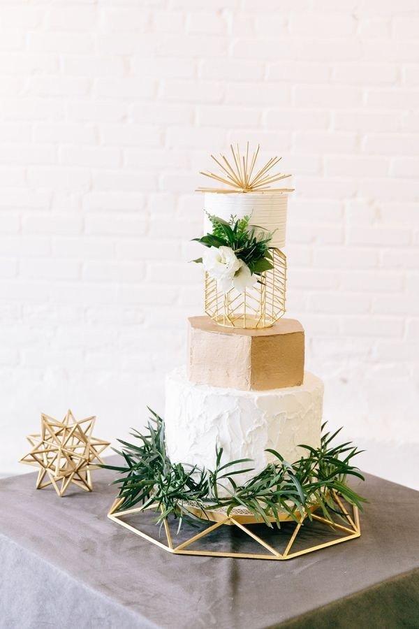 modern metallic gold white and greenery wedding cake