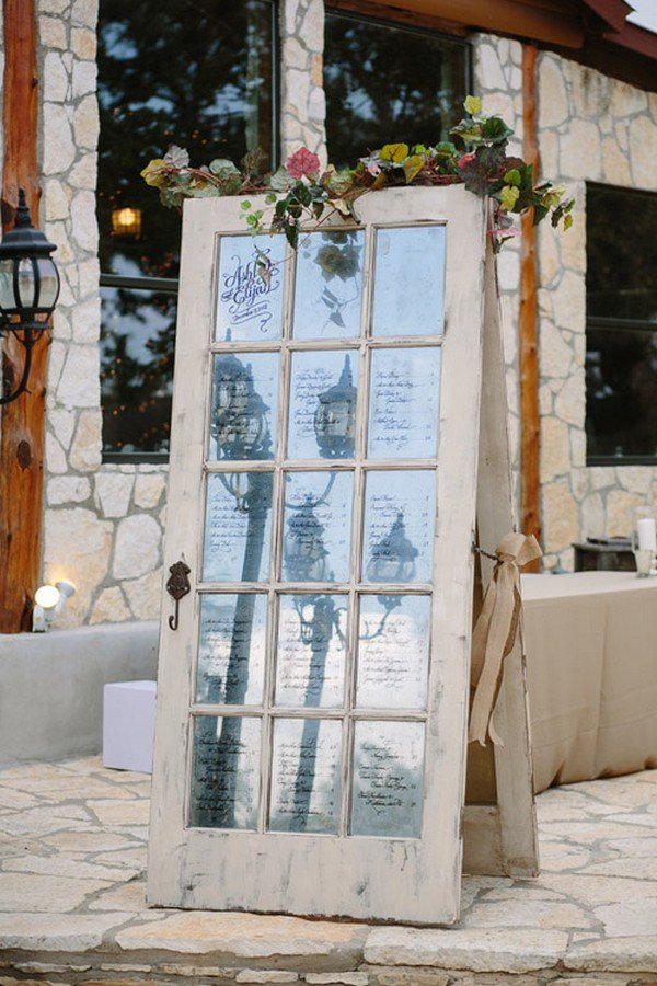 rustic and vintage inspired door with seating chart written on glass panes