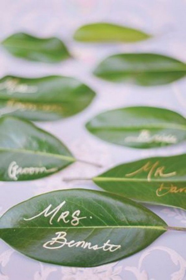 gold calligraphy on green leaves wedding seating plan ideas