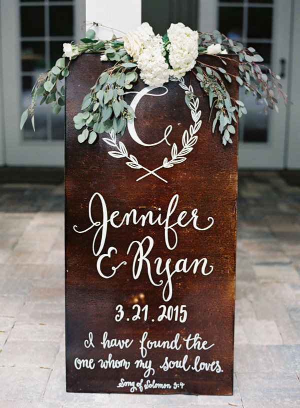 rustic wooden wedding signs with white and green floral decorations