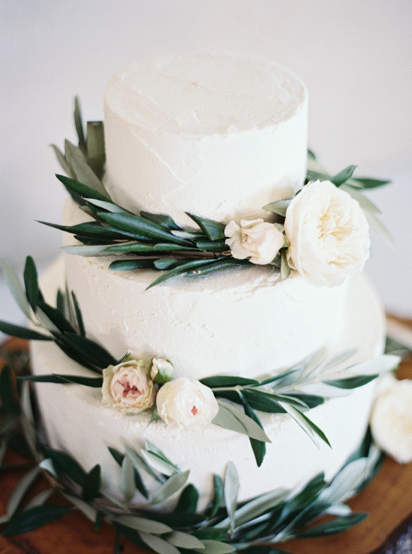 white wedding cake with greenery and pink floral