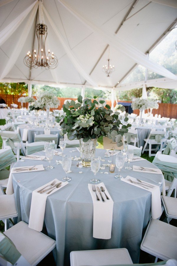 light blue and white wedding table settings with greenery centerpiece
