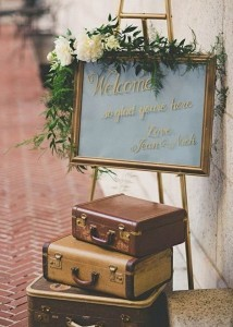 vintage travel themed wedding sign with suitcases