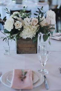 chic white and green wedding centerpiece with olive branch