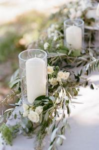 outdoor elegant wedding centerpiece with olive branch and candles