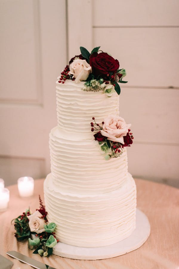 rose topped burgundy and blush fall wedding cake