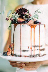 Caramel drip wedding cake with fresh fruit and flowers