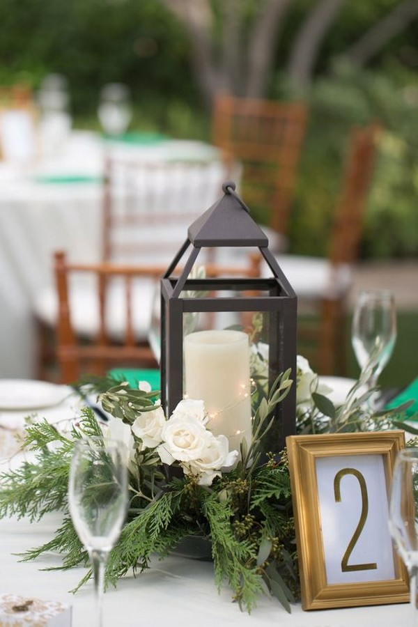 Green, white, and gold winter wedding centerpiece with lanterns