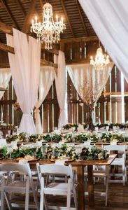 chic wedding reception with white draping in a barn