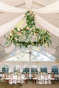 gorgeous tented wedding reception with floral chandelier and white draping