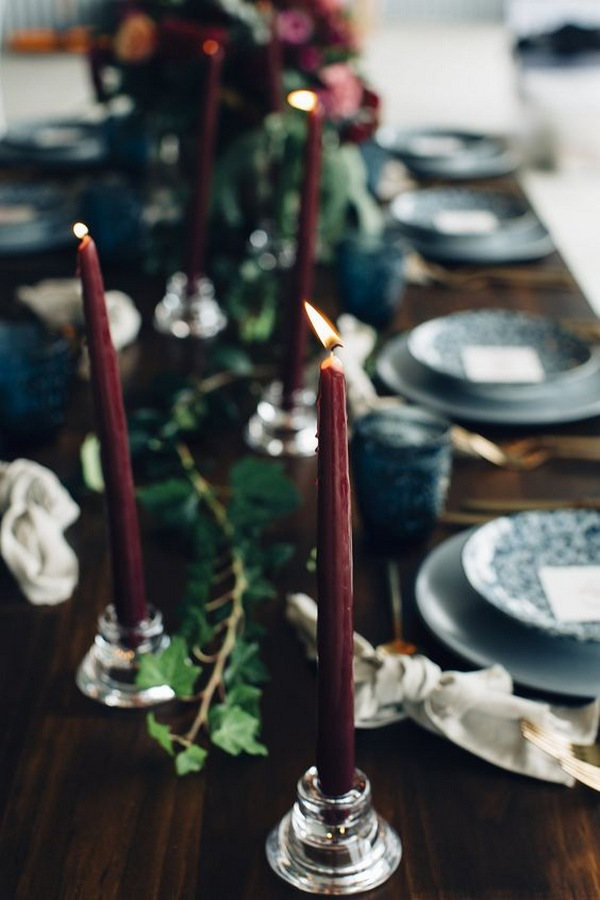 moody blue and burgundy wedding table decorations with long taper candles