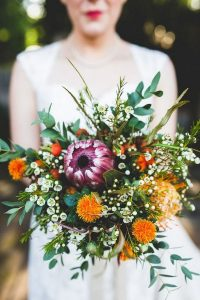 purple and orange wedding bouquet with proteas