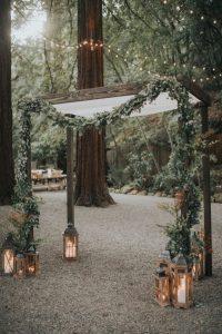 boho chic wedding arch ideas with garland and lanterns