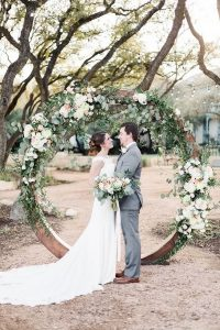 chic outdoor floral and wooden circular wedding arch