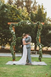 chic outdoor wedding arch with greenery garland