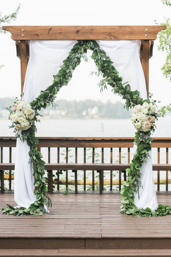 chic wedding ceremony arch with garland and fabric