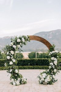 chic wooden circular wedding arch with white and green floral