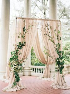 elegant outdoor wedding arch ideas with neutral drapery and greenery