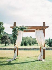 outdoor draped wedding ceremony arch