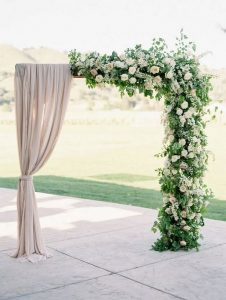 outdoor wedding floral arch with neutral drapery