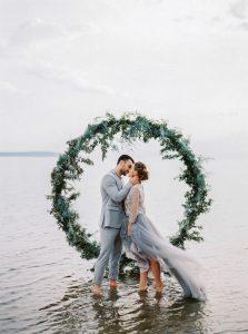 romantic wedding photo with greenery circular wedding backdrop