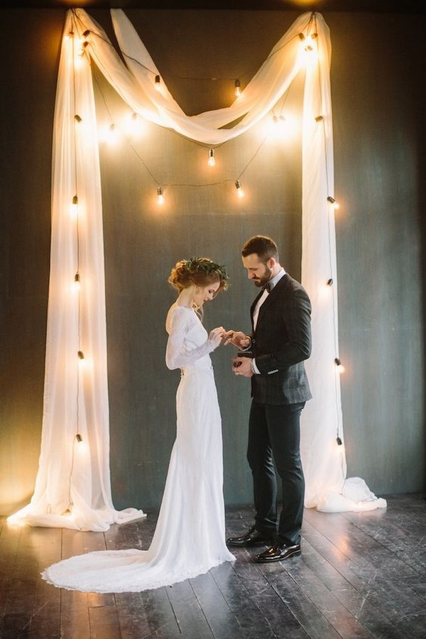 simple elegant wedding backdrop ideas with white draping and Edison Bulbs