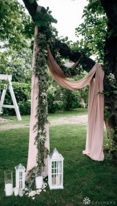wedding ceremony arch decorated with greenery and dusty rose drapery