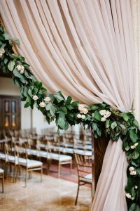 wedding entrance decoration ideas with dusty rose drapery and greenery garland