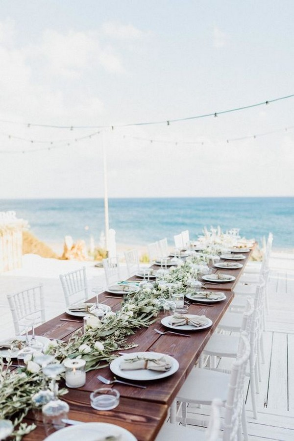beach wedding reception decorations with long table and greenery garland