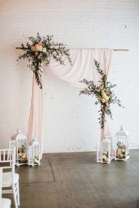 blush pink draping cloth and flowers wedding arch