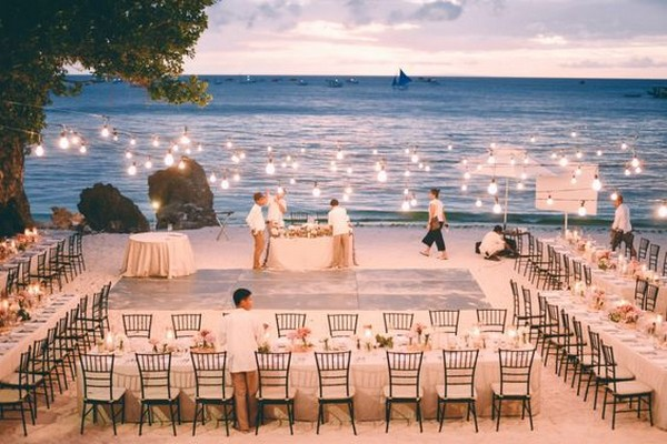 romantic beach wedding reception with string lights