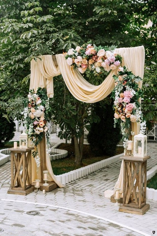 romantic wedding ceremony arch decorated with peach draping and pink roses