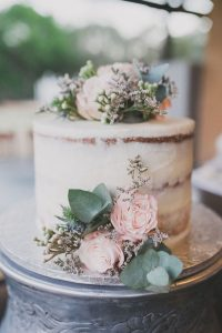 semi naked simple wedding cake with pink flowers