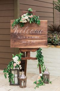 chic wooden wedding welcome sign with lanterns