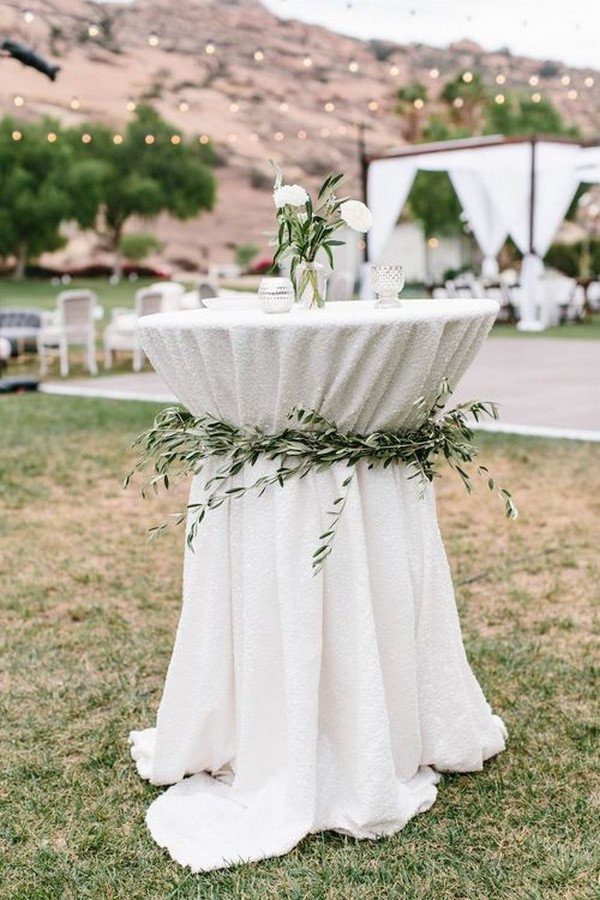 elegant wedding cocktail table decorated with olive leaves