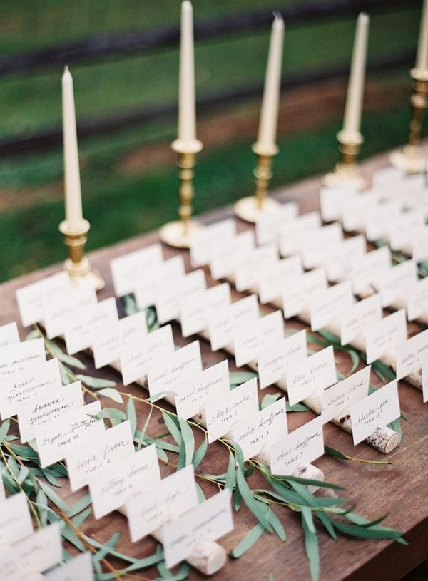 wedding escort card table decorated with greenery and candles