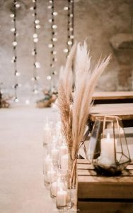 romantic wedding aisle decorations with candles and pampas grass