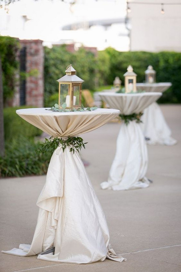 backyard wedding cocktail table with lantern decorations