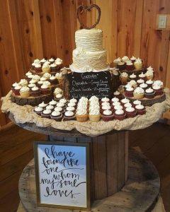 country wedding cake with cupcakes around