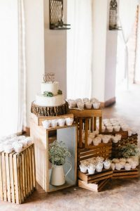 rustic wedding cake display with cupcakes