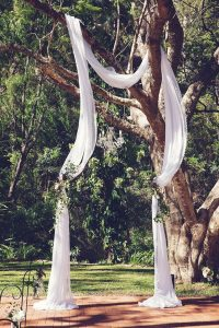 outdoor wedding arch ideas with drapery hung on a tree