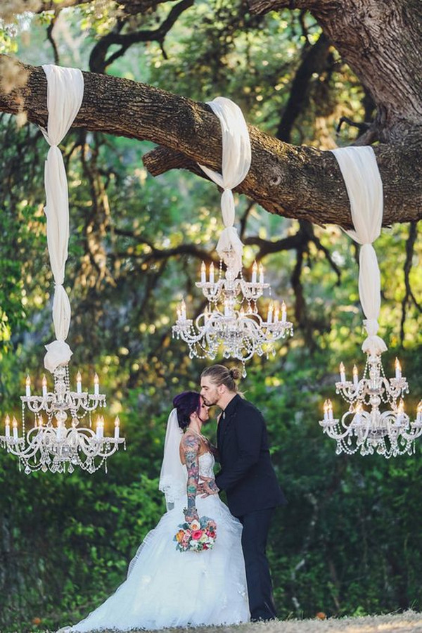unique wedding backdrop with chandeliers hung on a tree