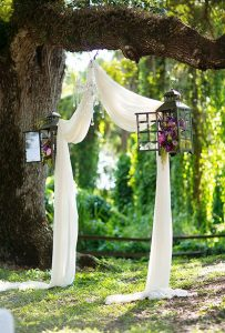 wedding altar ideas with drapery and lanterns hung on a tree