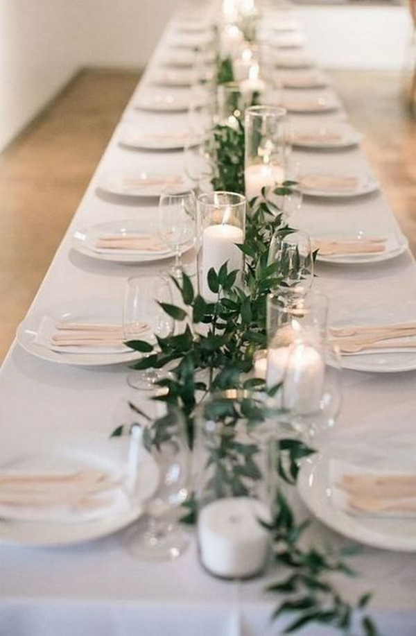 simple elegant wedding centerpiece with greenery and candles