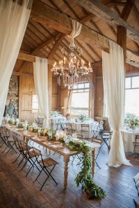 barn wedding reception decor ideas with draping fabric and greenery table runner
