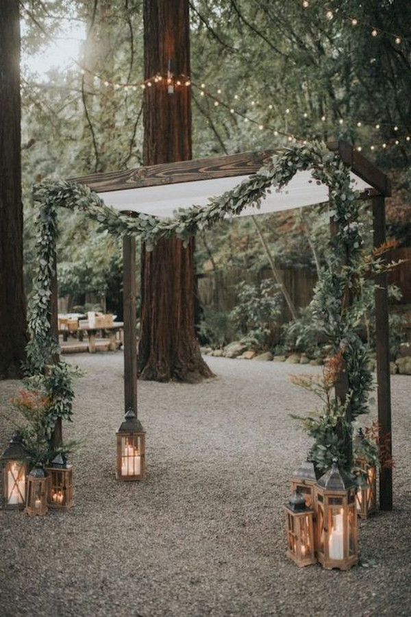 chic forest wedding arch ideas with lanterns